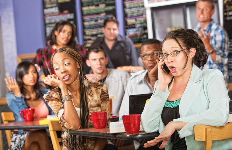 Talkative Woman in Cafe. Talkative female on cell phone annoying students in cafe stock photography