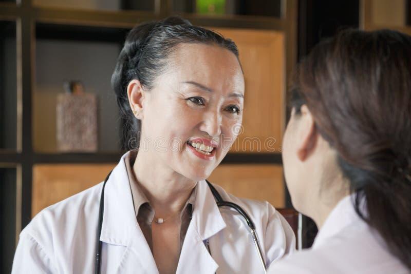 医治Talking与患者,在肩膀视图 库存图片
