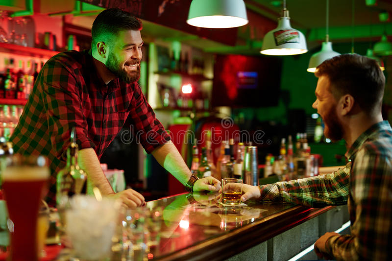 Talking in bar. Happy barman talking to client in bar royalty free stock photo