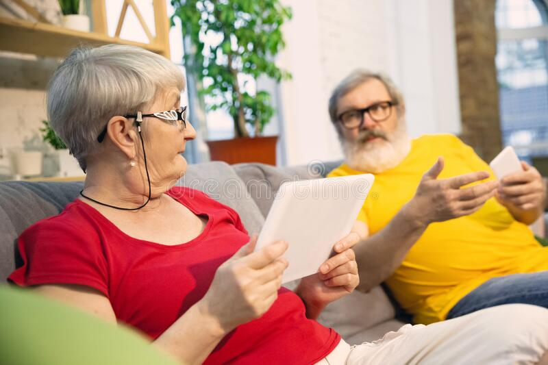 Couple of seniors spending time together being quarantined - caucasians mature and retired man and woman using modern royalty free stock images