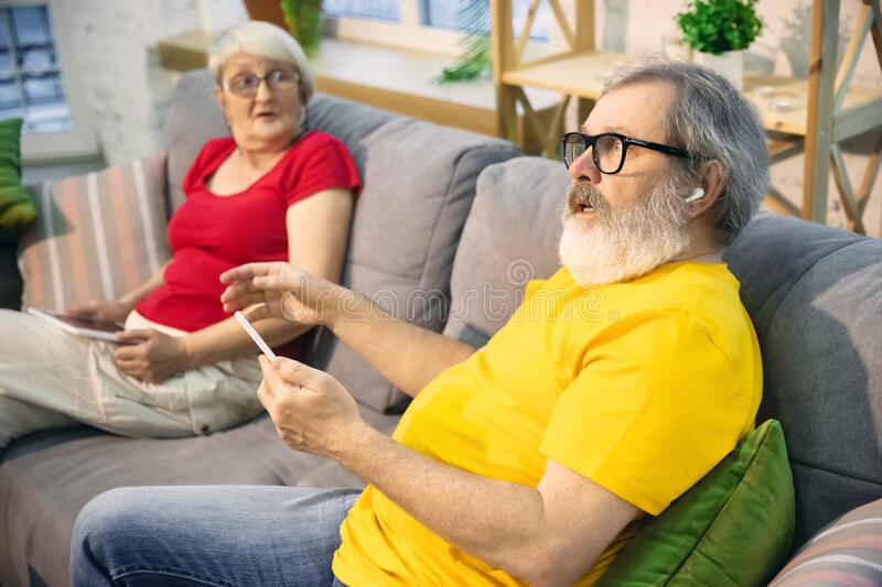 Couple of seniors spending time together being quarantined - caucasians mature and retired man and woman using modern stock image