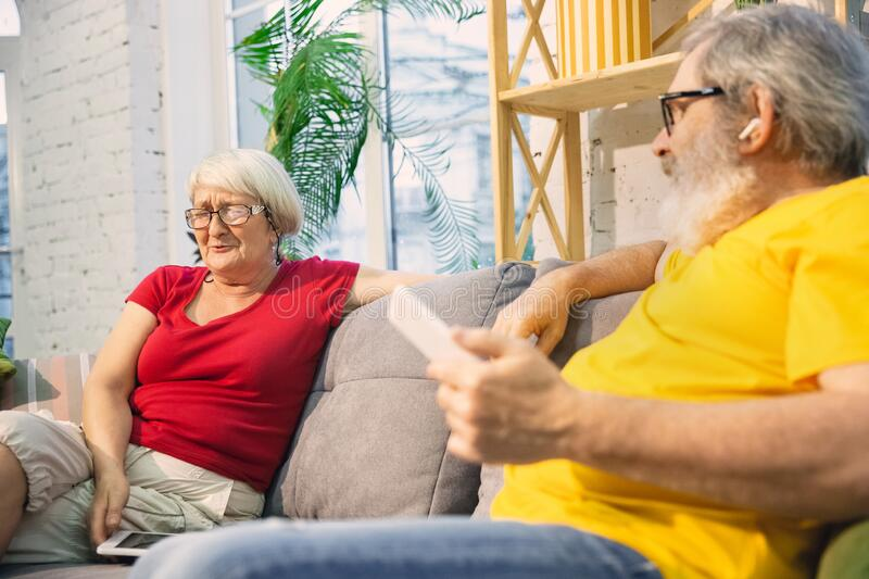Couple of seniors spending time together being quarantined - caucasians mature and retired man and woman using modern royalty free stock photography