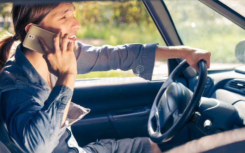 Man talking on phone while driving car. Talking while drive, danger fresh driver concept. Young man driving car using his smartphone, talking with someone royalty free stock photo