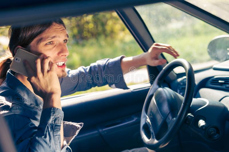 Man talking on phone while driving car. Talking while drive, danger fresh driver concept. Young man driving car using his smartphone, talking with someone stock photo