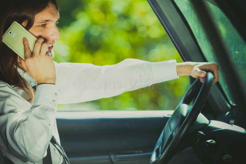 Man talking on phone while driving car. Talking while drive, danger fresh driver concept. Young man driving car using his smartphone, talking with someone royalty free stock images