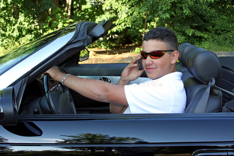 Talking and Driving. A young man talking on his cell phone and driving at the same time stock photography