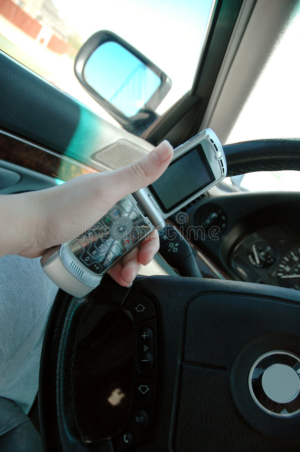 Talking and Driving. Driver talks on the speaker phone while driving a car royalty free stock photography