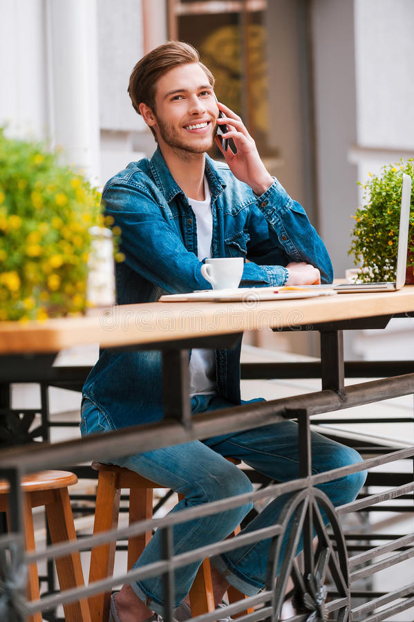 Talking with friends. Happy young man talking on the mobile phone and smiling while sitting at sidewalk cafe stock photo