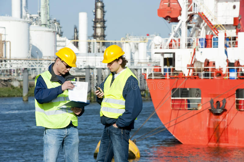 Talking Harbor workers. Two harbor workers going over docking plans in at a petrochemical port royalty free stock photography