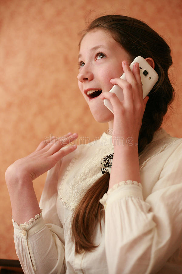 Talking by her cellular. Girl teenager white with brown hair in a blouse and skirt, schoolgirl, received a phone as a present, very happy, calling a friend royalty free stock photos