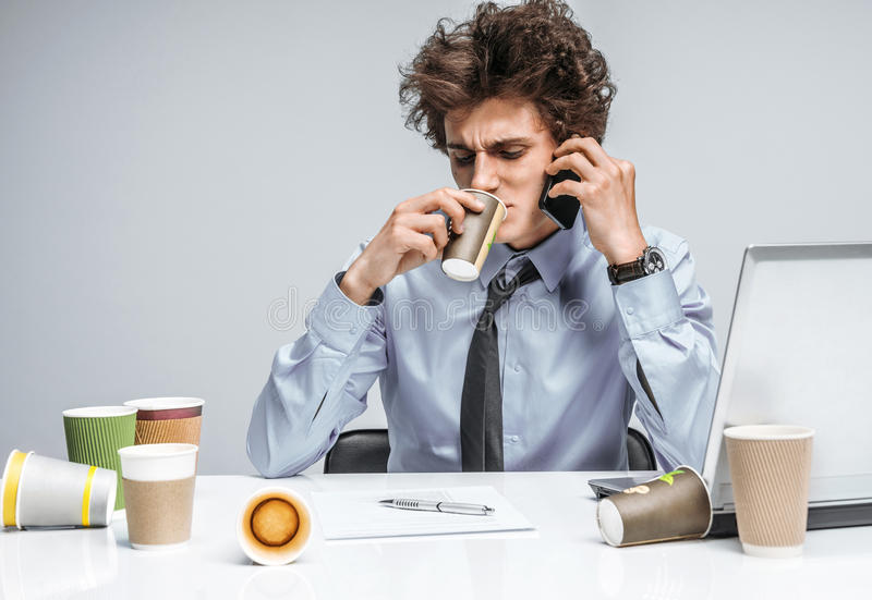 While talking intensely on a phone, manager sitting with a cup. Coffee and conversation: While talking intensely on a phone, manager sitting with a cup. Modern royalty free stock photo