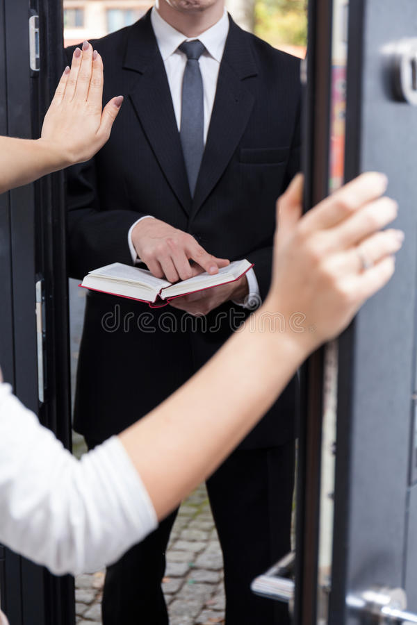 Talking Jehovah's witness to leave her house. Woman talking Jehovah's witness to leave her house royalty free stock images