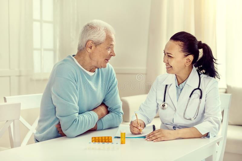 Positive minded elderly man and nurse discussing treatment royalty free stock photos