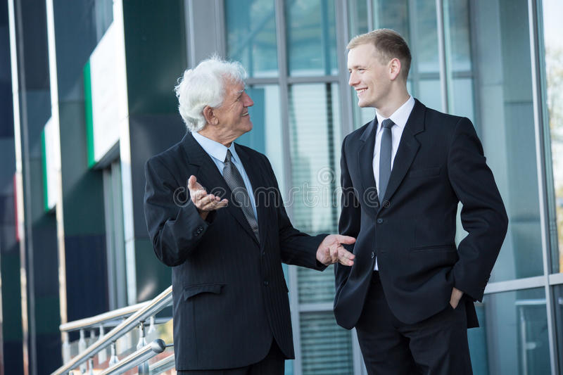 Talking outisde the buillding. Elderly director and young worker talking outside the building stock image