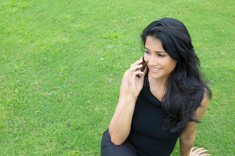 Talking outside. Closeup portrait, young, happy beautiful woman in black shirt sitting, speaking on cell phone, outside outdoors green grass background. Good stock images