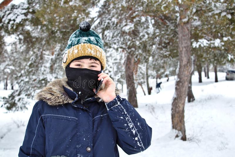 Talking on the phone boy in a knitted hat with a bubo and balaclava on a winter. Walk stock photos