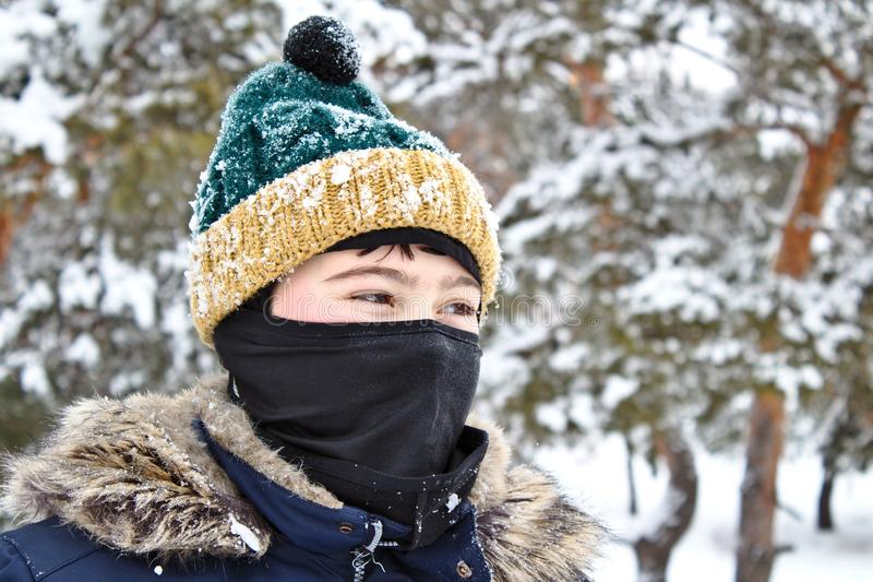Talking on the phone boy in a knitted hat with a bubo and balaclava on a winter walk. Young, cold, happy, smile, man, background, portrait, mobile, jacket royalty free stock photo