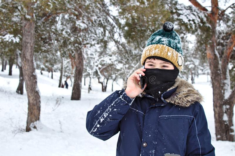 Talking on the phone boy in a knitted hat with a bubo and balaclava on a winter walk. Young, cold, happy, smile, man, background, portrait, mobile, jacket stock photography