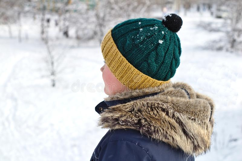 Talking on the phone boy in a knitted hat with a bubo and fur hood on a winter walk. Young, cold, happy, smile, man, background, portrait, fashion, beautiful royalty free stock image