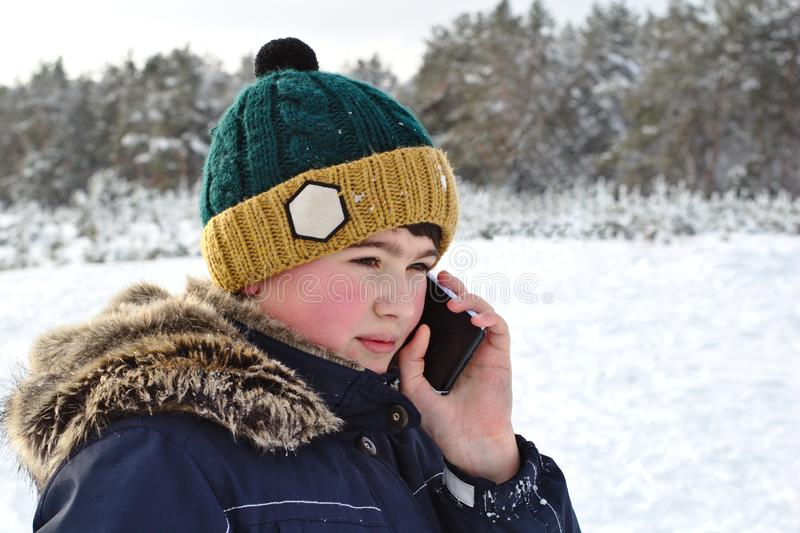 Talking on the phone boy in a knitted hat with a bubo and fur hood on a winter walk. Young, cold, happy, smile, man, background, portrait, fashion, beautiful royalty free stock images