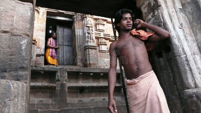 Talking on the phone. India. Bhubaneshwar, India: A man talking on the phone at the gate of a temple of Bhubaneshwar stock photo