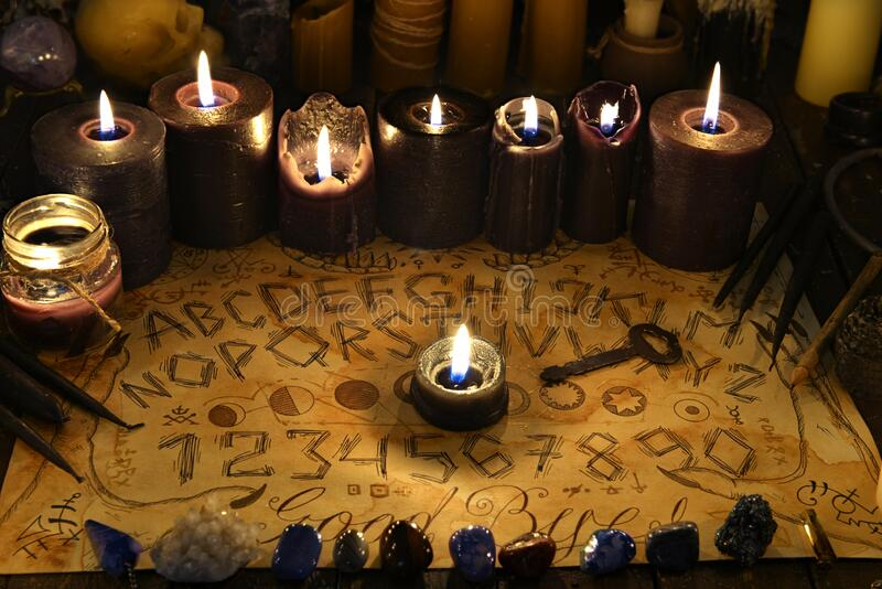 Talking spiritual board with black candles and old key stock images
