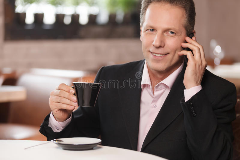 Talking to business partner. Cheerful businessman drinking coffee and talking at phone while sitting at restaurant stock photography