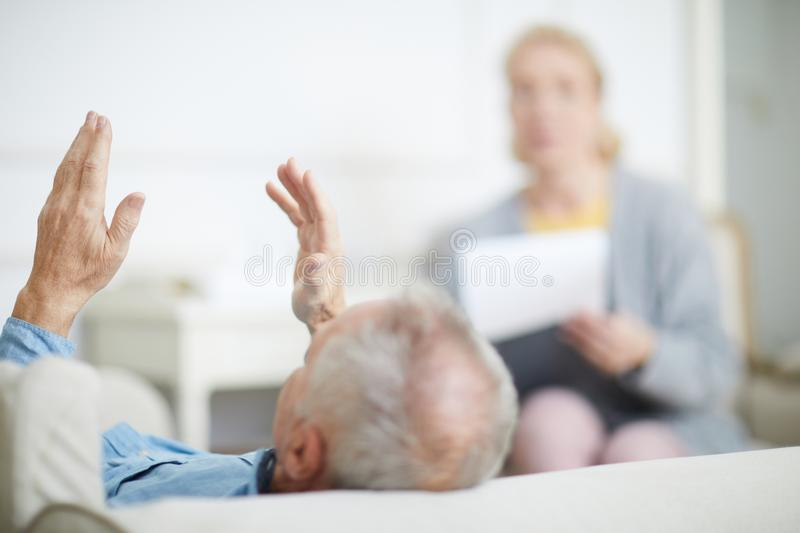 Talking to counselor. Senior patient of psychologist lying on couch and telling about his problems to counselor royalty free stock photo