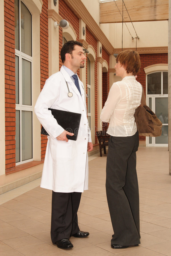 Talking to the doctor. A young woman and a male doctor stand outside a building, having a conversation royalty free stock images