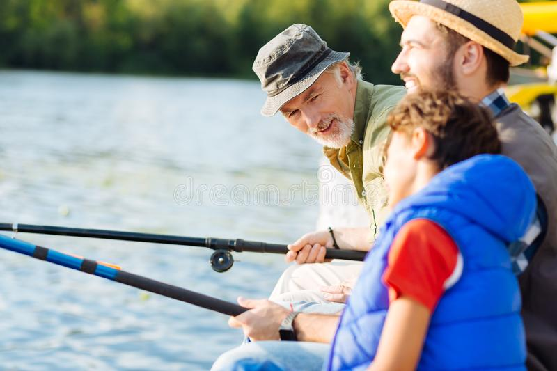 Grandfather talking to grandson while having family fishing royalty free stock photos
