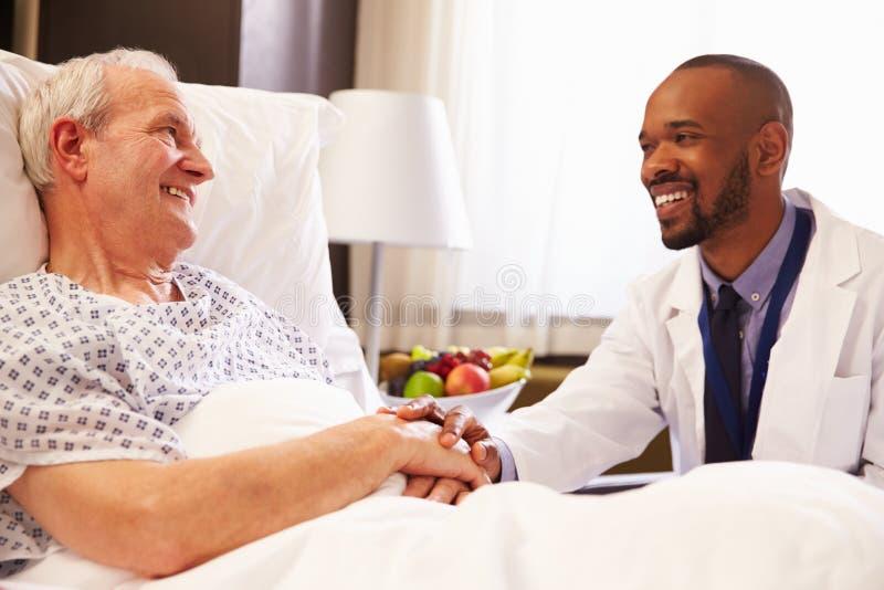 Talking To Senior Male医生患者在医院病床上 免版税图库摄影