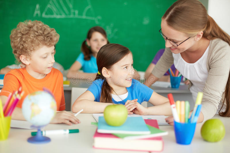 Talking to teacher. Portrait of diligent schoolkids and teacher interacting at lesson stock photography
