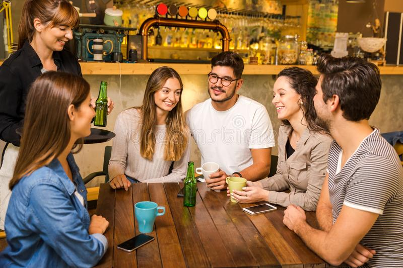 Talking to the waitress. A group of friends making a order at cafe royalty free stock photography