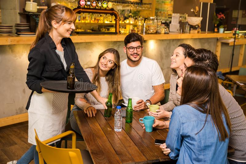 Talking to the waitress. A group of friends making a order at cafe royalty free stock images