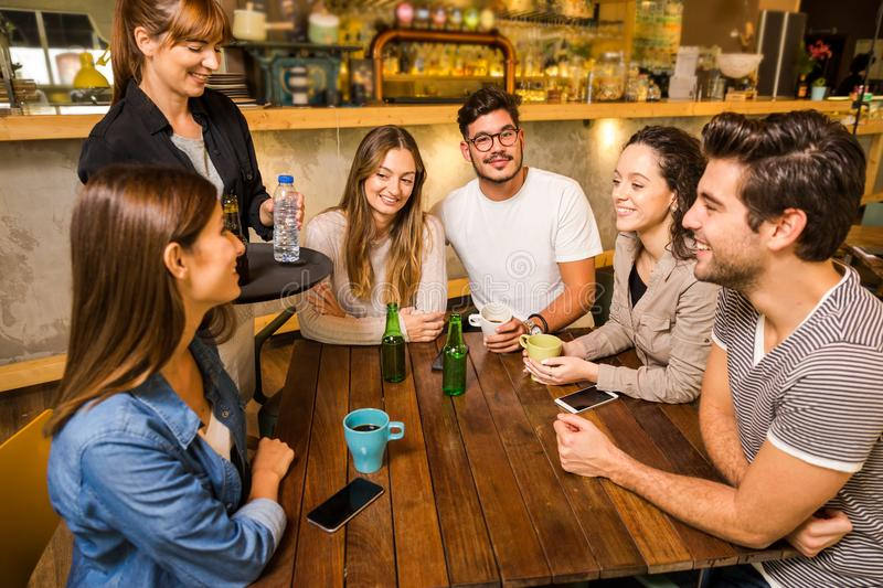 Talking to the waitress. A group of friends making a order at cafe stock photography