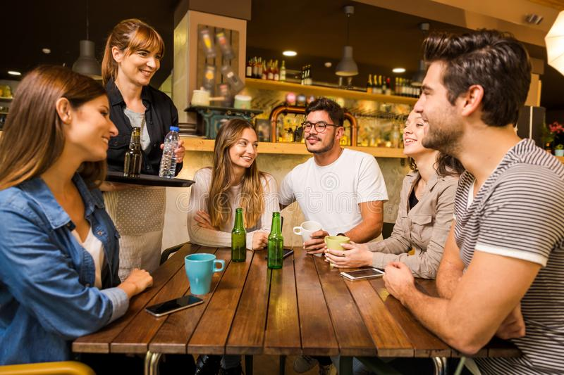 Talking to the waitress. A group of friends making a order at cafe royalty free stock image