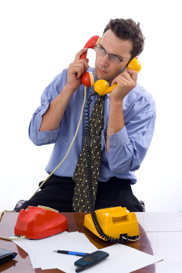 Talking on two telephones. Busy businessman talking on two telephones in the same time royalty free stock photos