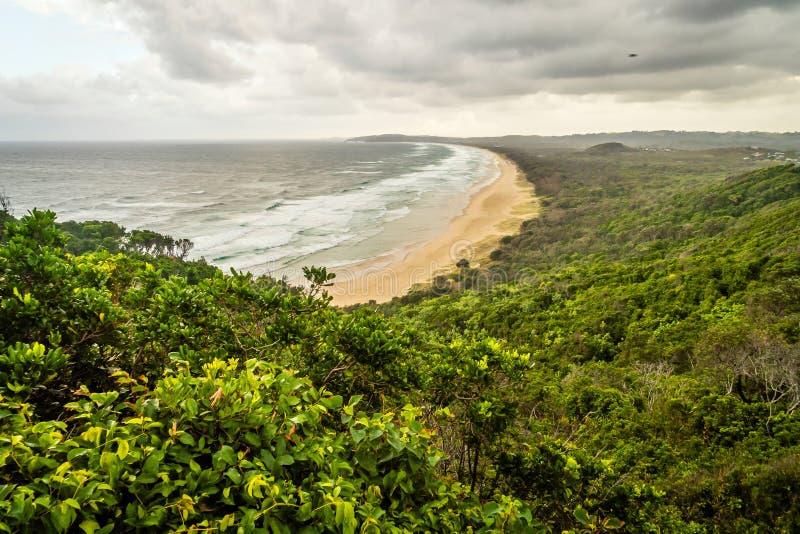 Talkstrand in Byron Bay in Australië op een bewolkte dag stock afbeelding