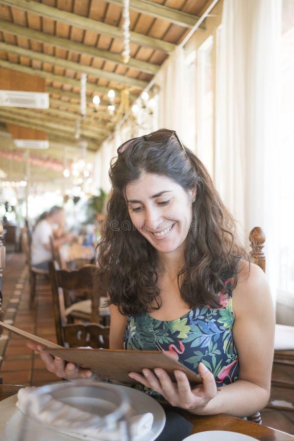 30-talkvinna i restaurangen som ser menyn fotografering för bildbyråer