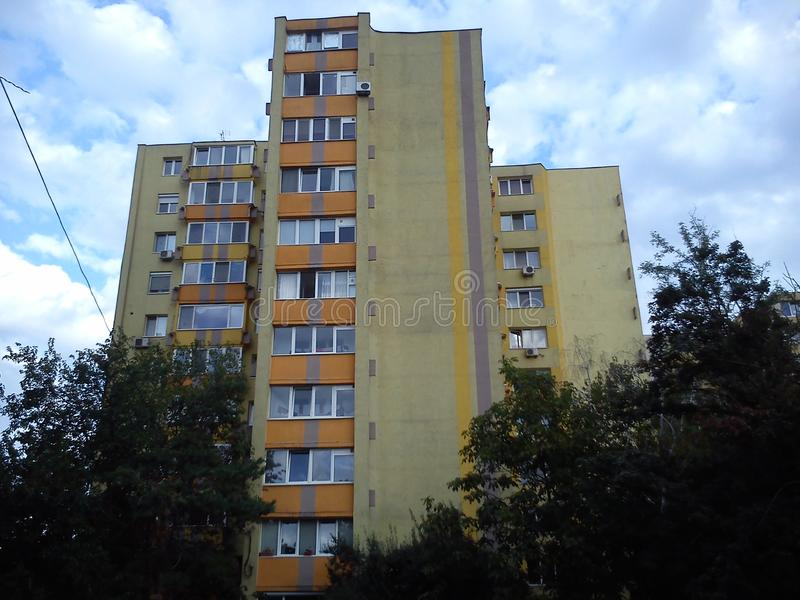 Tall apartment building of the late socialism era. Yellow facade, balconies and loggias, residential condition. Blue sky with light clouds, trees. Timisoara royalty free stock images