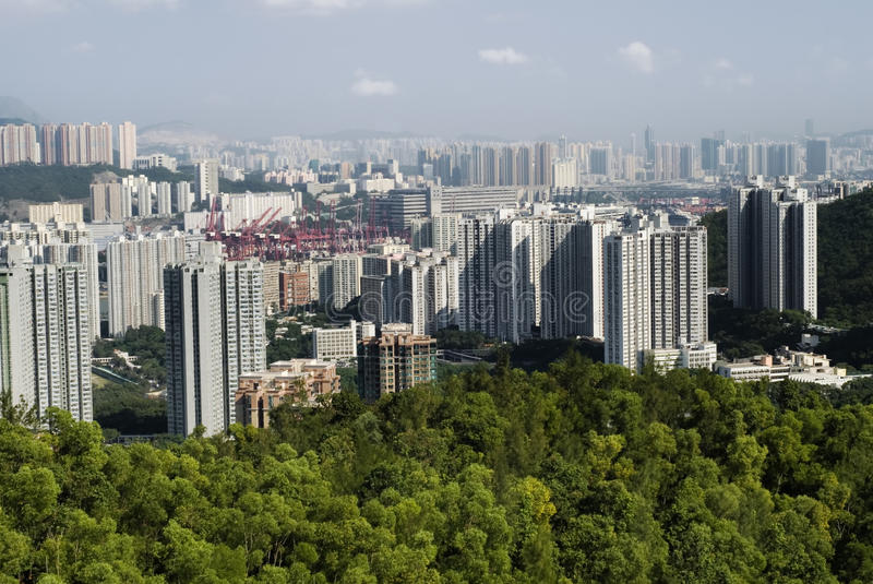 Tall apartments with green mountain and blue sky stock image