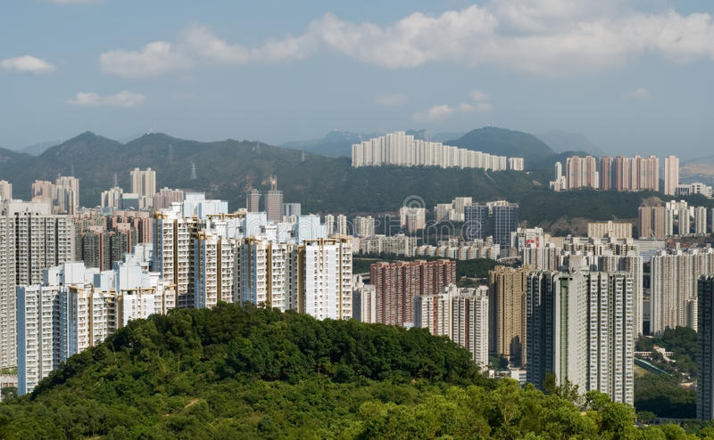 Tall apartments with green mountain and blue sky stock photography