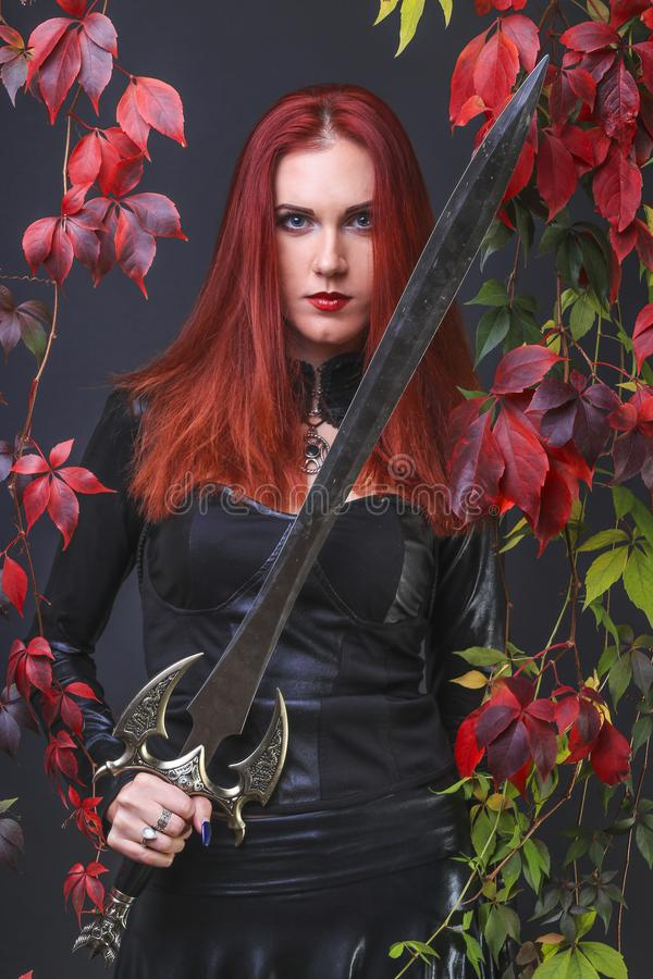 Tall beautiful red head girl wearing black leather outfit holding a fantasy sword surrounded with autumn color leaves foliage. Fantasy portrait stock photo