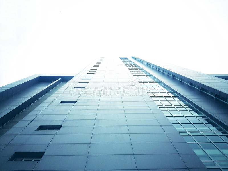 The tall building from the bottom view has a white sky background royalty free stock photography