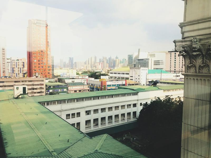 Tall buildings on the city of Manila with white roman column on the right.  stock photo