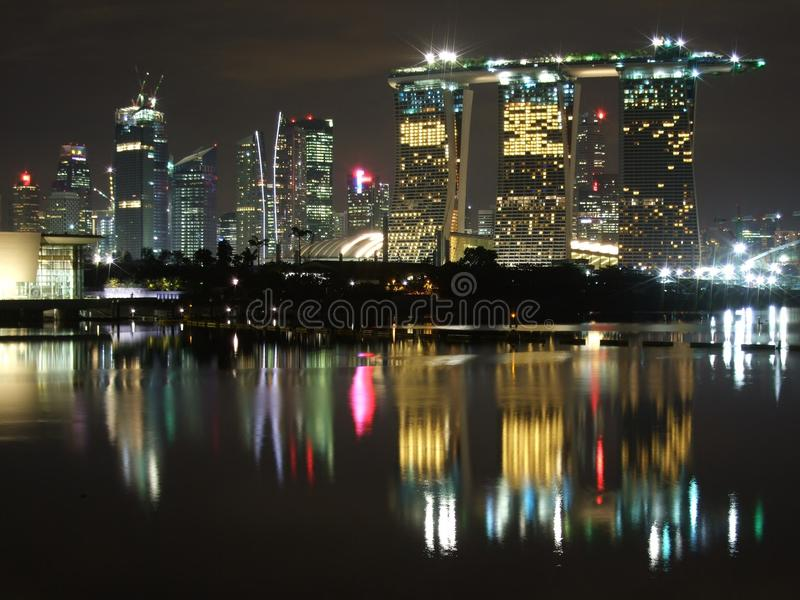 Tall buildings and light reflections at Marina Bay. View of tall buildings and their light reflections at Marina Bay, by night royalty free stock images