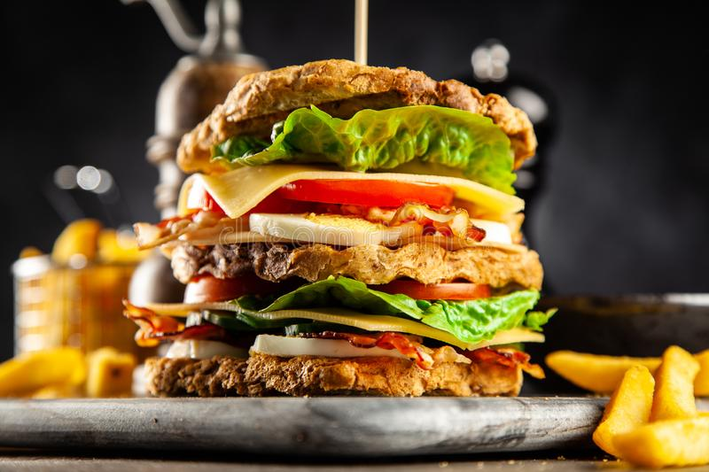 Tall club sandwich. And french fries stock photos