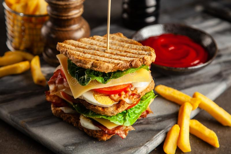 Tall club sandwich. And french fries royalty free stock images