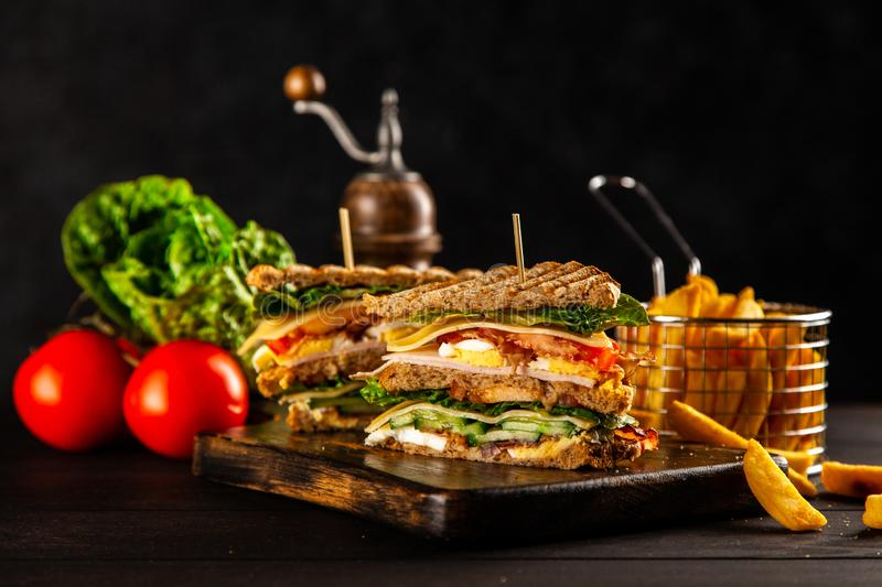 Tall club sandwich. And french fries stock images