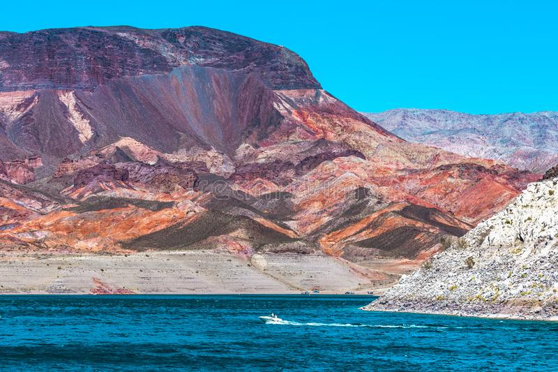 A Tall Colorful Rock Formation at Lake Mead with a Boat stock photo